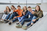 Summer holidays and teenage concept - group of smiling teenagers with skateboard hanging out outside. - 166731989