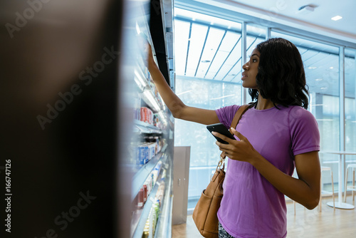 Woman in convenience store on cell phone