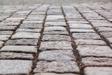 Close up view on the road pavement bricks. Old cobblestone walkway