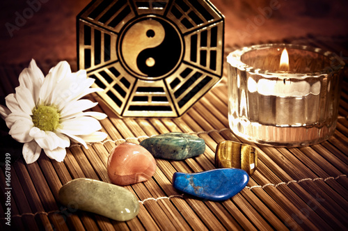 Ying yang, i-ching with healing stones, candle and a daisy flower like a concept of chinese oriental astrology  © starblue