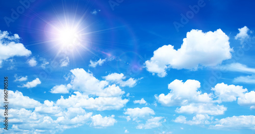 Sunny background, blue sky with white clouds and sun - 166790536