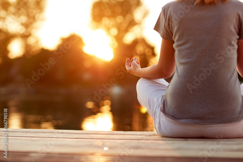 Wall mural Yoga near water at sunset- body part