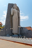 Huge Buddha stand upright in the sanctuary with Buddhist monastery and Hindu temple in the small town Dondra, Sri Lanka. The town is known as city of gods