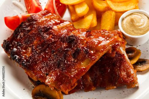 Deurstickers Klaar gerecht Grilled ribs, French fries and vegetables on white background