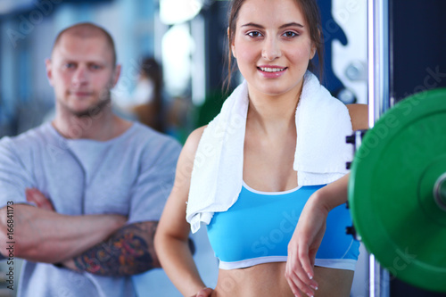 Sticker Beautiful woman at the gym exercising with her trainer. Beautiful woman. Gym