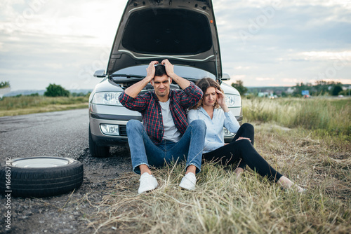Tired man and woman sitting against broken car.