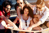 Group of beautiful best friends are together choosing a new destination on the map. - 166858735