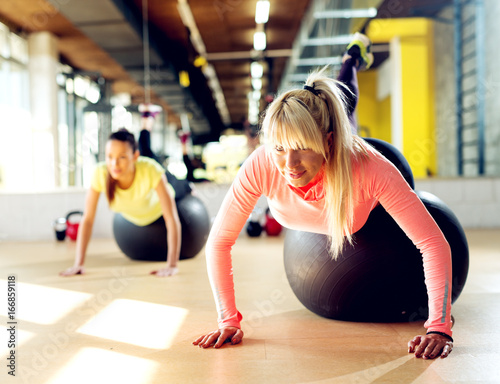 Beautiful young sporty women working out with a black fitness ball.