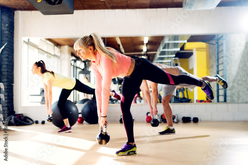 Beautiful young sports people are working out with kettlebell in gym.