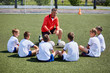 Coach Instructing Junior Football Team in Practice
