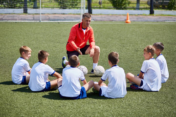 Coach Instructing Junior Football Team in Practice