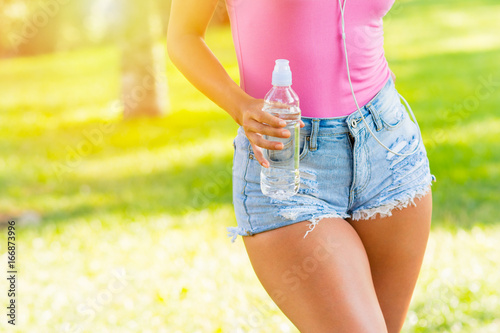 Young woman with plus size thighs in denim shorts in park holding a bottle of water