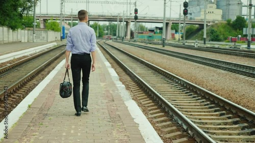 Rear view: A young successful businessman walks along the railway station along the tracks. He carries a bag in his hand, smiles. A successful business trip