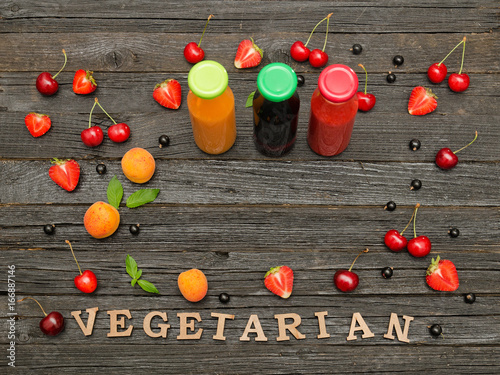 Poster Sap Three bottles with juice, fruit and inscription vitamins on a wooden background, food concept