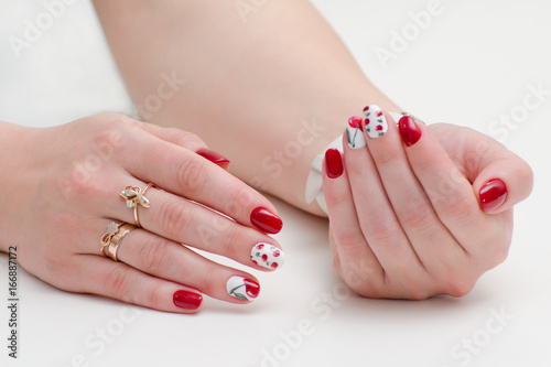 Female hands with manicure, red nail polish, drawing with cherries. White background.