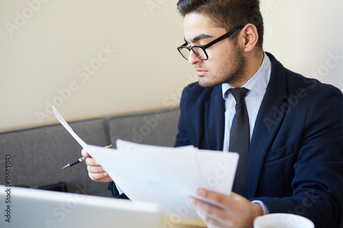 Young economist looking through papers at workplace
