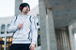 Active young man in hoodie and beanie listening to music in urban environment