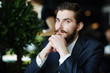 Постер, плакат: Serious and elegant entrepreneur with curled moustache looking at camera