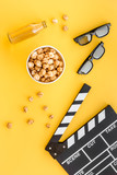 Snacks for film watching. Popcorn and soda near clapperboard, glasses on yellow background top view - 166903939