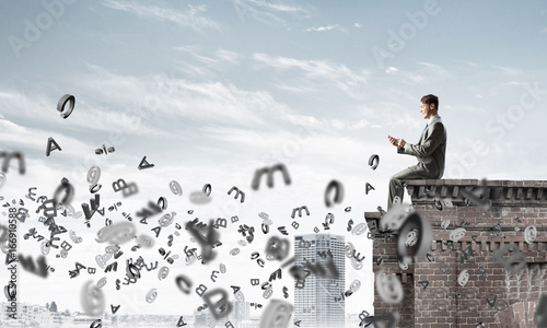 Wall mural Man on roof edge send message with smartphone and symbols flying around