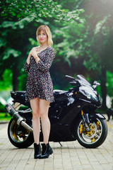 Blonde girl with a sports bike in a dress, tender summer photo