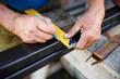 Man measuring off metal bar in workshop.