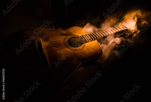 Music concept. Acoustic guitar isolated on a dark background under beam of light with smoke with copy space. Guitar Strings, close up. Selective focus. Fire effects - 166921336