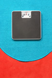 Bathroom scale on blue and red carpet. Background for leaflets and web sites on slimming and dieting theme. - 166923781