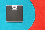 Bathroom scale on blue and red carpet. Background for leaflets and web sites on slimming and dieting theme. - 166923965
