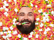 Bearded guy holding birthday whistle in candies
