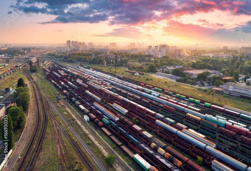 Widok z lotu ptaka kolorowi pociągi towarowi. Stacja kolejowa. Pociągi towarowe. Wagony z towarami na kolei. Przemysł ciężki. Przemysłowa scena z pociągami, miasto budynkami i chmurnym niebem przy zmierzchem ,. Widok z góry