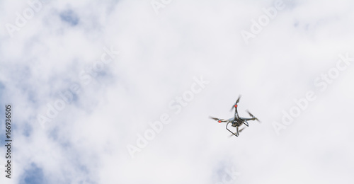Juliste white drone hovering in a bright blue sky