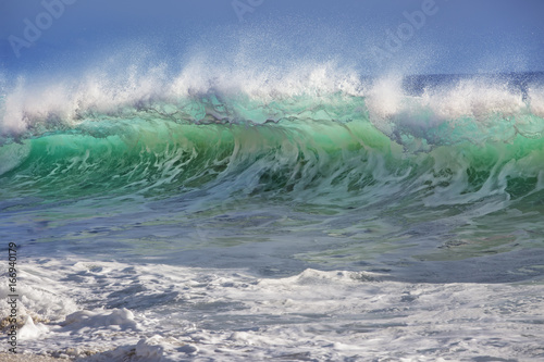 Bright colorful surfing ocean wave. Tropical background in sunset colors for sport activity with nobody on image.