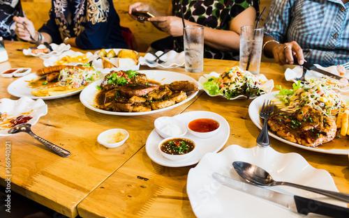 people meeting eating steak and salad