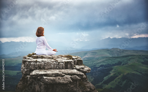 Wall mural woman practices yoga and meditates in   lotus position on mountains, peak