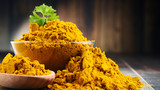 Composition with bowl of curry powder on wooden table - 166949754