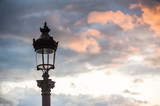 Parisian lamppost against clouds at sunset, France