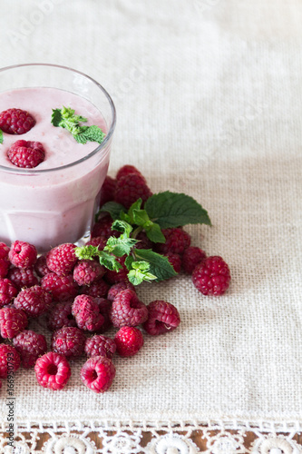 Glass smoothies made of banana and raspberries on a background of raspberries