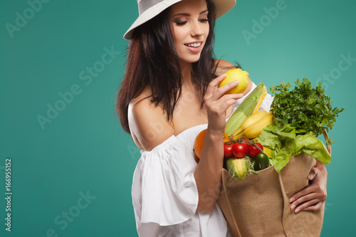 Sticker Young woman holding grocery paper shopping bag full of fresh vegetables. Diet healthy eating concept