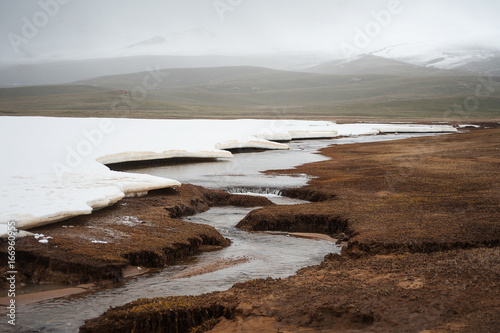 Arctic wilderness, tundra, minimalistic landscape with Mountain river. Crystal blue huge ice on mountain river in May. Winding mountain river in spring landscape