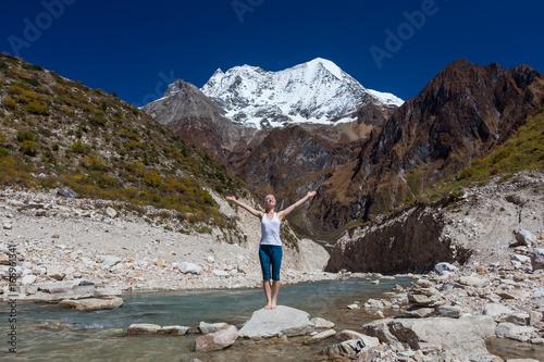 Sticker Woman is doing yoga excercises near big lake on the Manaslu circuit trak in Nepala