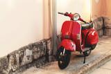 Czerwony skuter scooter zaparkowany w pobliżu ściany budynku - na zewnątrz strzału