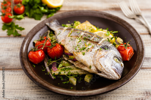 Baked whole fish, served with roasted vegetables and lemon. - 166974135