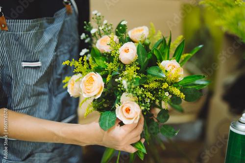 Male florist making beautiful bouquet at flower shop