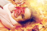 beautiful happy woman lying on autumn leaves - 166992301