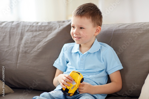 happy little boy with toy car at home