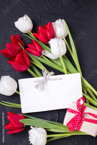 Bright red and white tulips flowers, empty tag and  wrapped box with present Poster