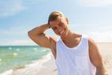 smiling young man on summer beach