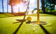 Mini Golf yellow ball with a bat near the hole at sunset