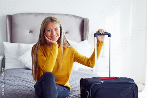 Woman with suitcase sitting on bed in hotel
